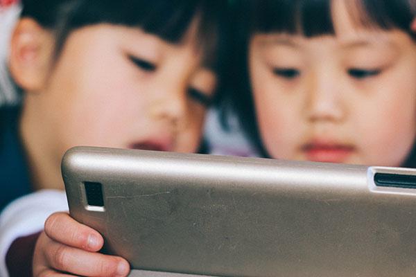 タブレットを見ている子供たち