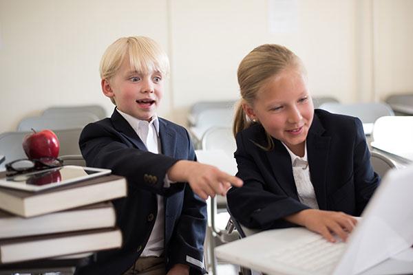 ブロンドの少年少女がパソコンを見ている