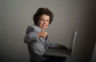 パソコン片手にGOODポーズの少年