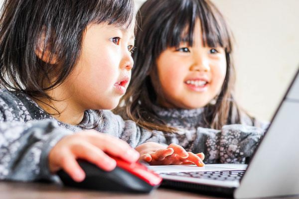 パソコンを見て微笑む少女二人
