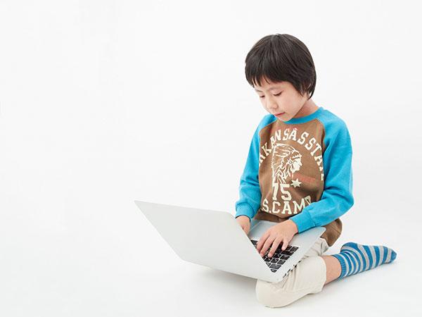 正座してパソコンを触る少年