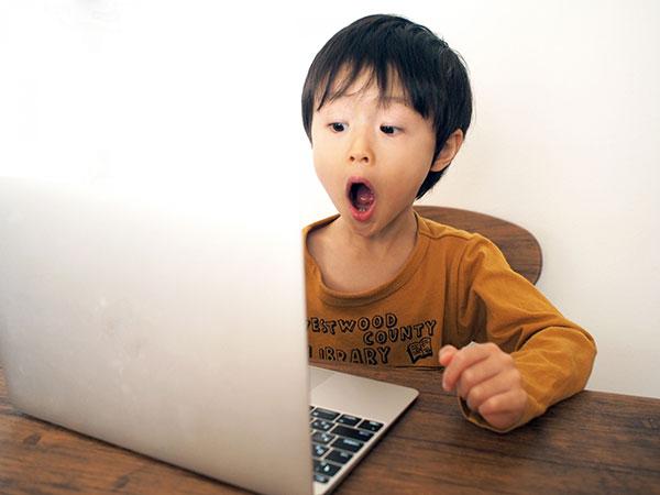 パソコンを見て驚く少年